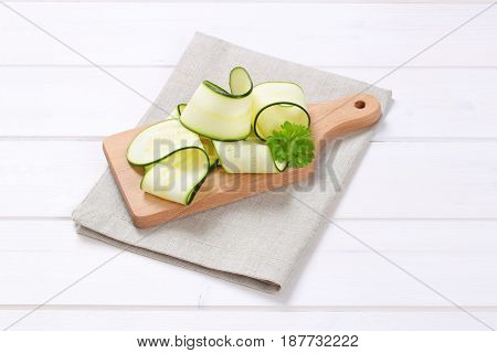 pile of raw zucchini strips on wooden cutting board