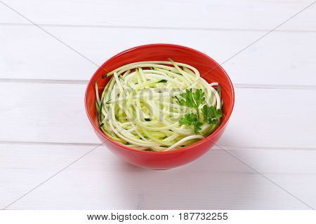 bowl of raw zucchini noodles on white wooden background