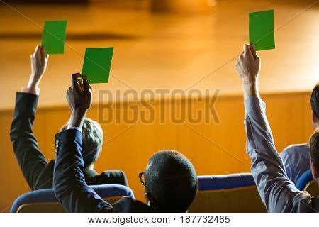 Rear view of business executives show their approval by raising hands at conference center
