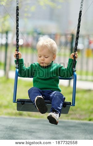 Portrait of toddler child outdoors. One year old baby boy wearing green sweater at playground swing