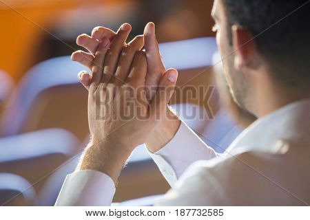 Business executive clapping while listening to speech at conference center