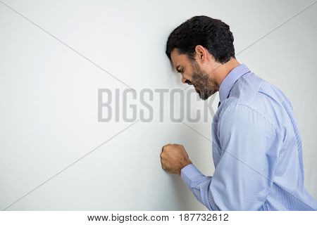 Worried and stressed businessman with hand on wall at conference centre