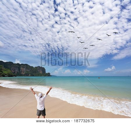 A lone tourist enthusiastically welcomes the new day at the beach
