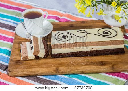 Three-layer chocolate cake, decorated with chocolate patterns.  Holiday cake Three-colate. Background - white vase with flowers and porcelain cup with hot tea. Professional bakery