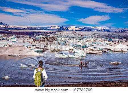 The woman - tourist with green backpack watching the sunrise in Ice Lagoon. The concept of extreme northern tourism. Ice floes are reflected in the water