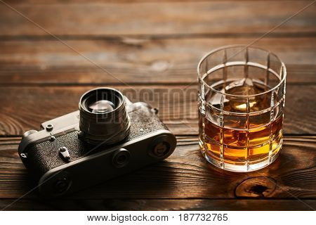 Glass of whiskey and vintage old 35mm rangefinder camera on wooden background