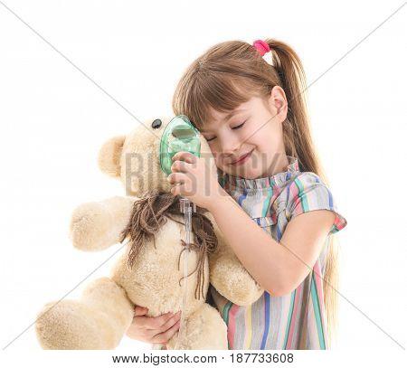 Cute little girl holding toy and nebulizer on white background. Allergy concept