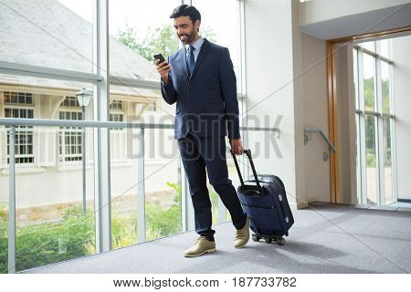 Businessman with trolley bag using mobile phone at conference centre