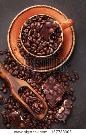 Coffee cup with roasted beans and chocolate on stone background. Top view