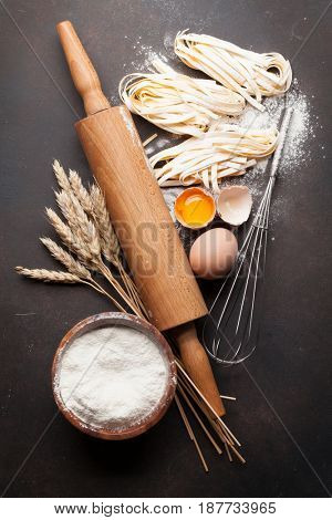 Pasta cooking ingredients on wooden kitchen table. Top view