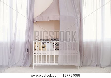 Crib with canopy near windows in baby room