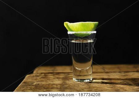 Tequila shot with juicy lemon slice and salt on dark background