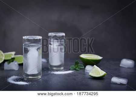 Tequila shots with juicy lime and salt on grey background