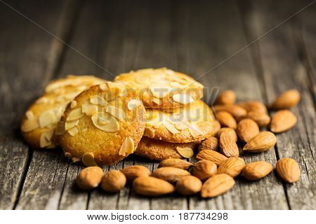 Sweet almond cookies on old wooden table. Black background.