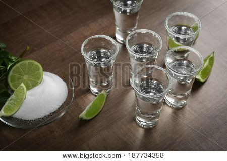 Tequila shots with juicy lime and salt on wooden background