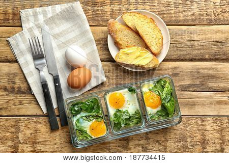Delicious eggs Florentine in glass baking dishes on wooden table