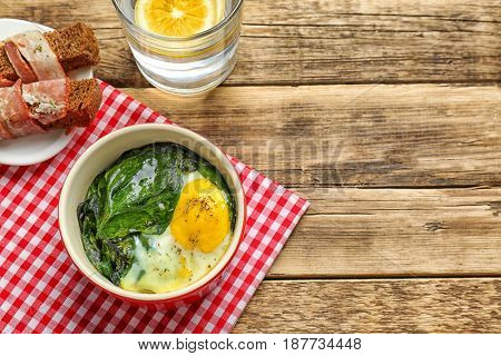 Delicious eggs Florentine in bowl and napkin on wooden table