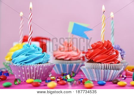 Tasty cupcakes with candles on colorful background