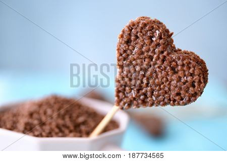 Heart shaped crispy dessert in cup on blue background