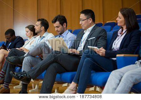 Business executives participating in a business meeting using electronic devices at conference center