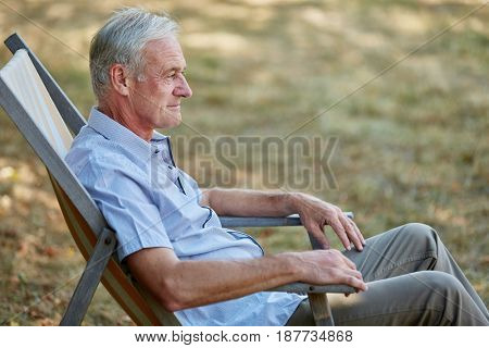Old man sitting relaxed on a deck chair in summer in the nature