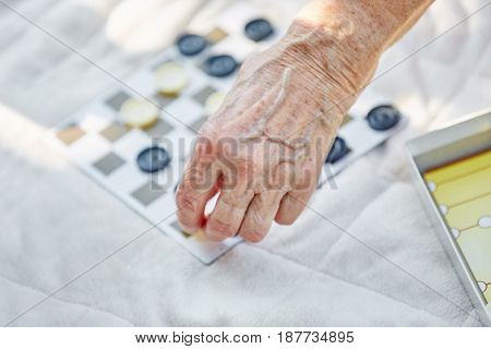 Senior lady playing a board game in the garden in summer