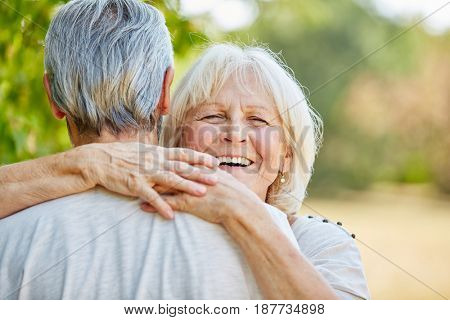 Smiling senior woman hugging a man in the nature in summer