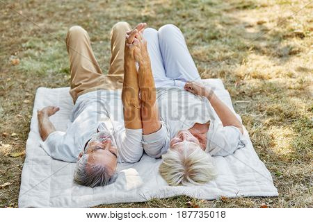 Happy senior couple hand to hand laying on a blanket in the garden