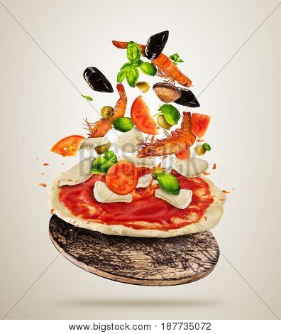 Concept of flying vegetable and sea food ingredients with pizza dough, isolated on gray background. Food preparation, fresh meal ready for cooking. Extra high resolution