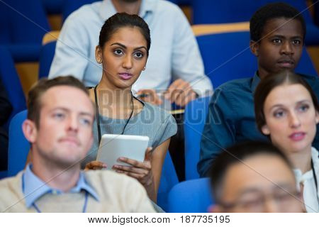 Business executive participating in a business meeting taking notes at conference center