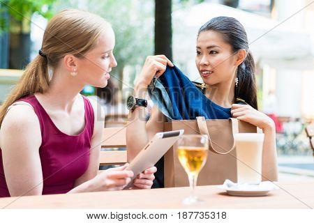 Two young women discussing a clothing purchase as they sit at a restaurant table ordering a meal as an attractive Asian women pulls it from the bag.