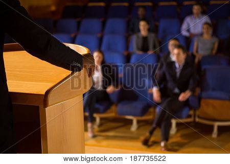 Mid section of male business executive giving a speech at conference center
