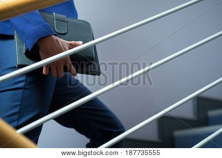 Mid-section of businesswoman with diary climbing up the stairs