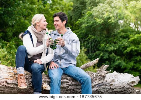 Happy lovers in vacation sitting at waterside on a trunk clinking beer bottles