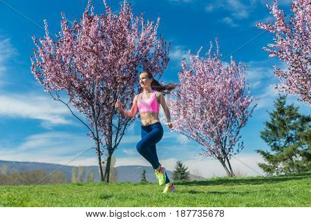 Woman in spring running or jogging as sport in spring park