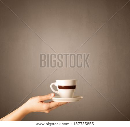 Young female hand holding coffee cup with brown background