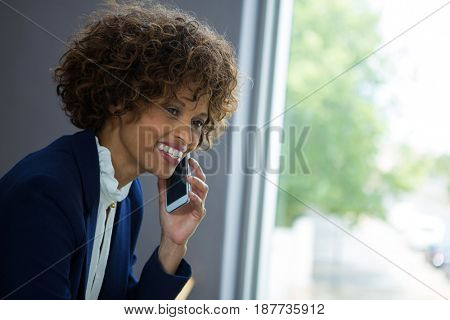 Businesswoman talking on mobile phone at conference centre