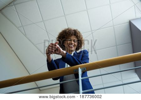 Businesswoman leaning over the railing of staircase at conference centre