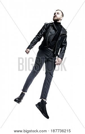 Fashion shot of a handsome brutal young man wearing black leather jacket and jeans. Male beauty, fashion. Isolated over white. Copy space.