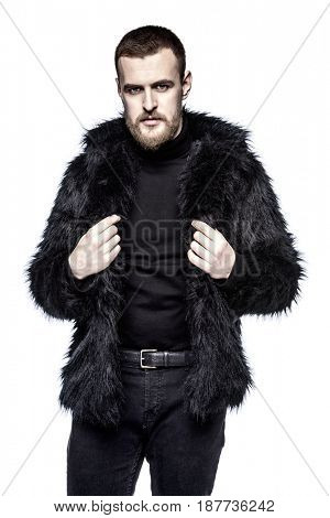 Fashion shot of a stylish bearded man wearing black fur jacket. Isolated over white.