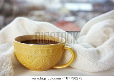 Patterned cup of hot tasty drink and fluffy scarf on windowsill