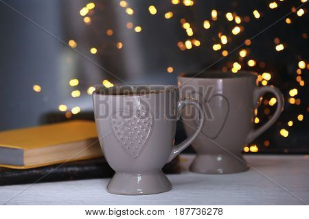 Cups of hot tasty drink with books on windowsill