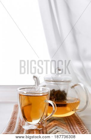 Glass cup of hot tasty drink with teapot and napkin on windowsill