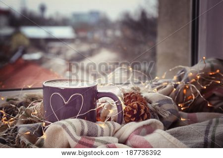 Cup of hot tasty coffee with garland and warm plaid on windowsill