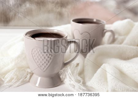 Cups of hot drink with shawl on windowsill