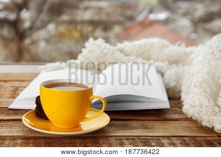 Yellow ceramic cup of hot tasty drink with open book on wooden windowsill