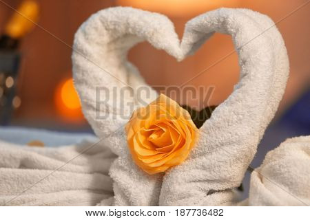 Two swans made of towels and rose flower on blurred background, closeup. Honeymoon concept