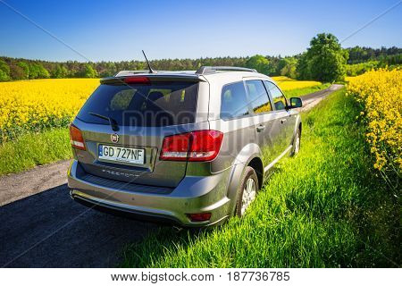 POLAND - MAY 18, 2017:  Fiat Freemont SUV at the blossom field in Poland. Fiat Freemont is an european version of Dodge Jurney manufactured sience 2011.