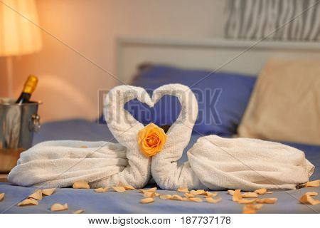 Two swans made of towels and rose petals on bed in hotel room. Honeymoon concept