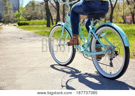 Young girl cycling in park on sunny day